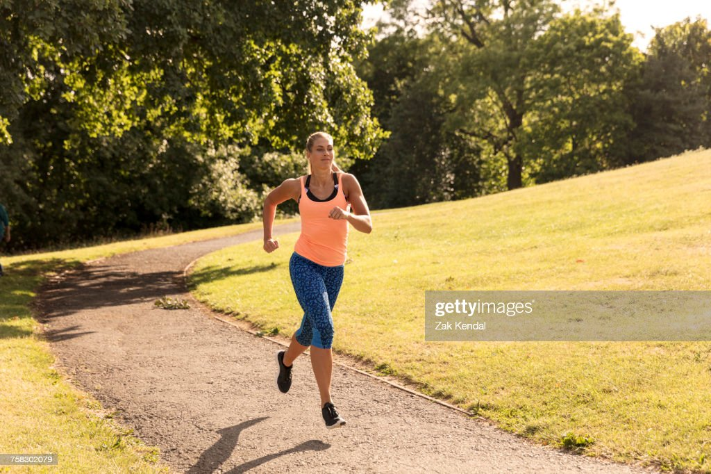 Young female runner running along park path : Stock Photo