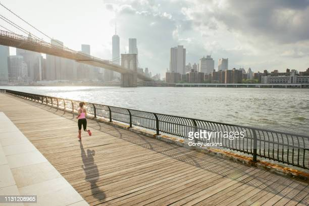 young female runner running along riverside, brooklyn, new york, usa - fool stock pictures, royalty-free photos & images
