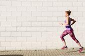 Young female runner running along sidewalk