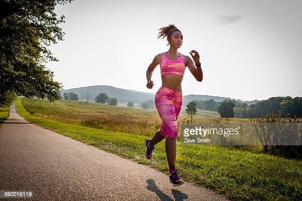 Young female runner running in rural park