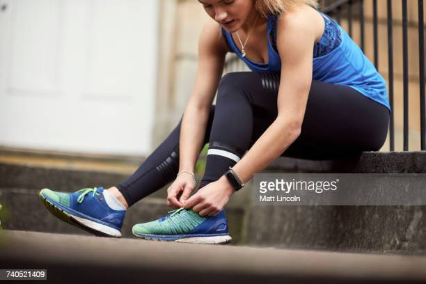 Young female runner sitting outside front door fastening trainer laces