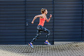 Young female runner speed running along sidewalk