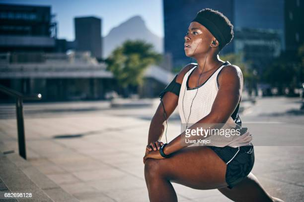 young female runner stretching - black shorts stock pictures, royalty-free photos & images