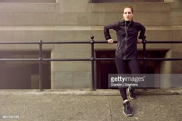 Young female runner taking a break on sidewalk