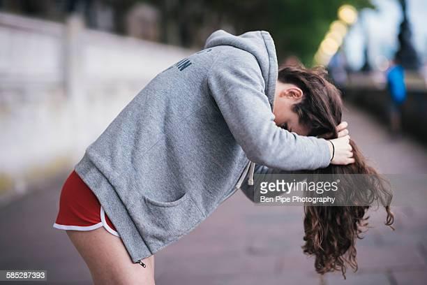 Young female runner tying up long hair on riverside