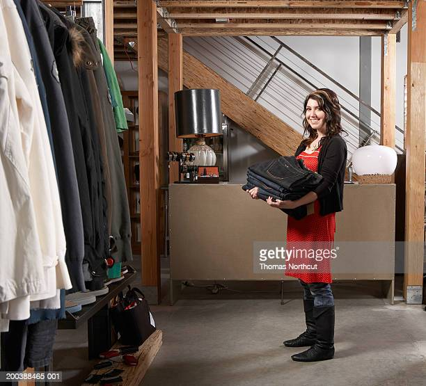 Young female sales clerk carrying stack of jeans in retail store