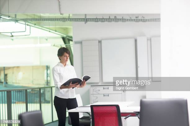 young female sales manager looking at sales brochure in office furniture store - sigrid gombert stock pictures, royalty-free photos & images