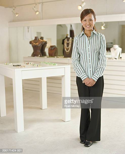 Young female salesclerk standing in jewelry store, smiling, portrait