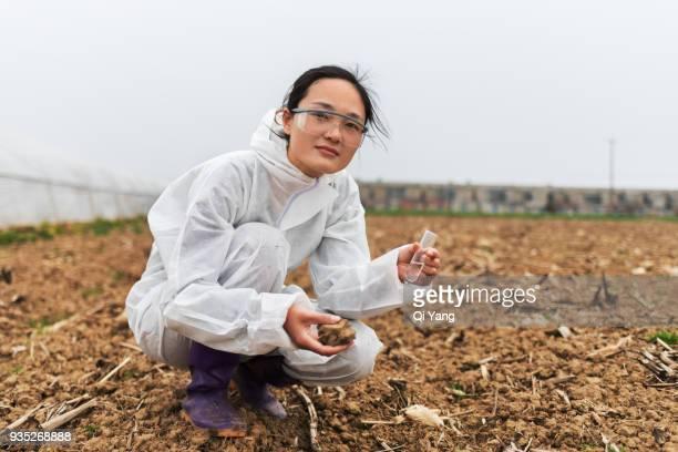 young female scientist holding test tube and soil - oggetti femminili foto e immagini stock