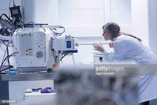 Young female scientist in lab using scanning electron microscope