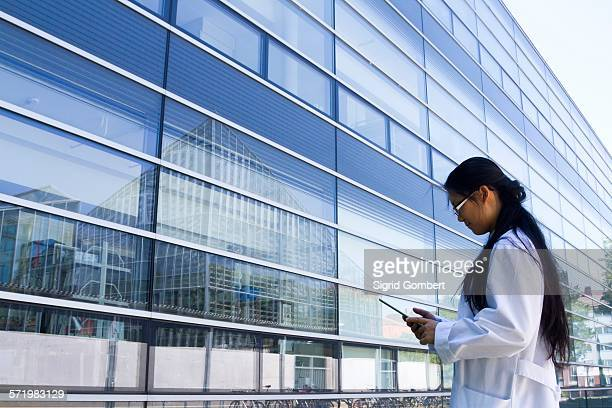 young female scientist looking at digital tablet outside laboratory - sigrid gombert stock-fotos und bilder