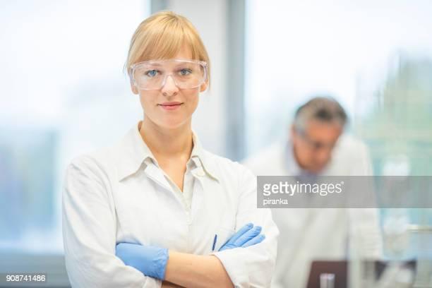 junge weibliche wissenschaftler - schutzbrille stock-fotos und bilder