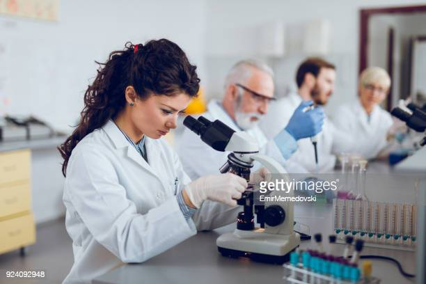 Young female scientist using microscope