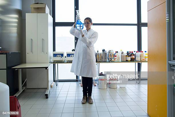 young female scientist with glass bulb standing in a chemical lab - laborkittel stock-fotos und bilder