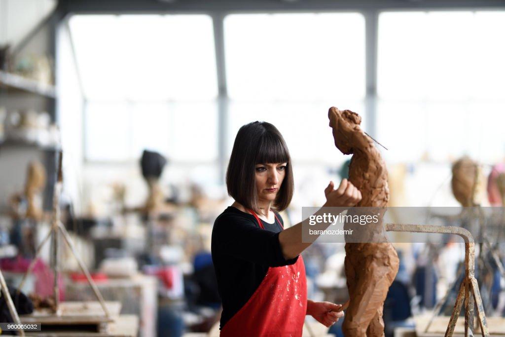 Junge weibliche Bildhauer arbeitet in ihrem Atelier : Stock-Foto