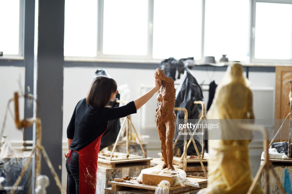 Young Female Sculptor is working in her studio : Stock Photo