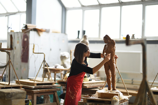 Young Female Sculptor is working in her studio 960077510
