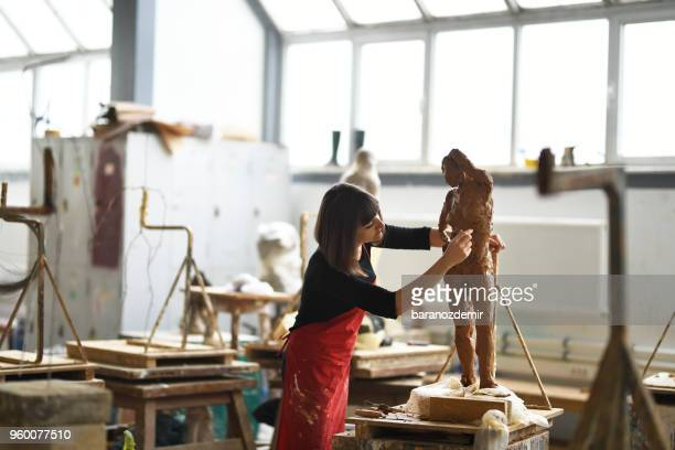 young female sculptor is working in her studio - sculpture stock pictures, royalty-free photos & images