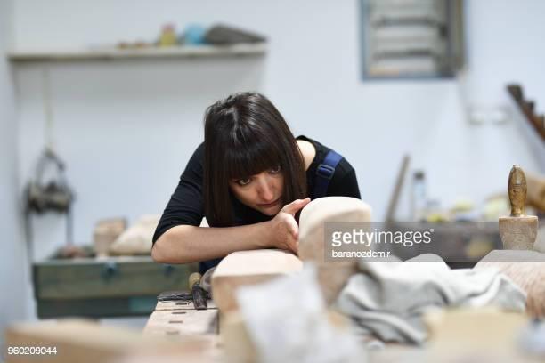 junge weibliche bildhauer arbeitet in ihrem atelier - bildhauer stock-fotos und bilder
