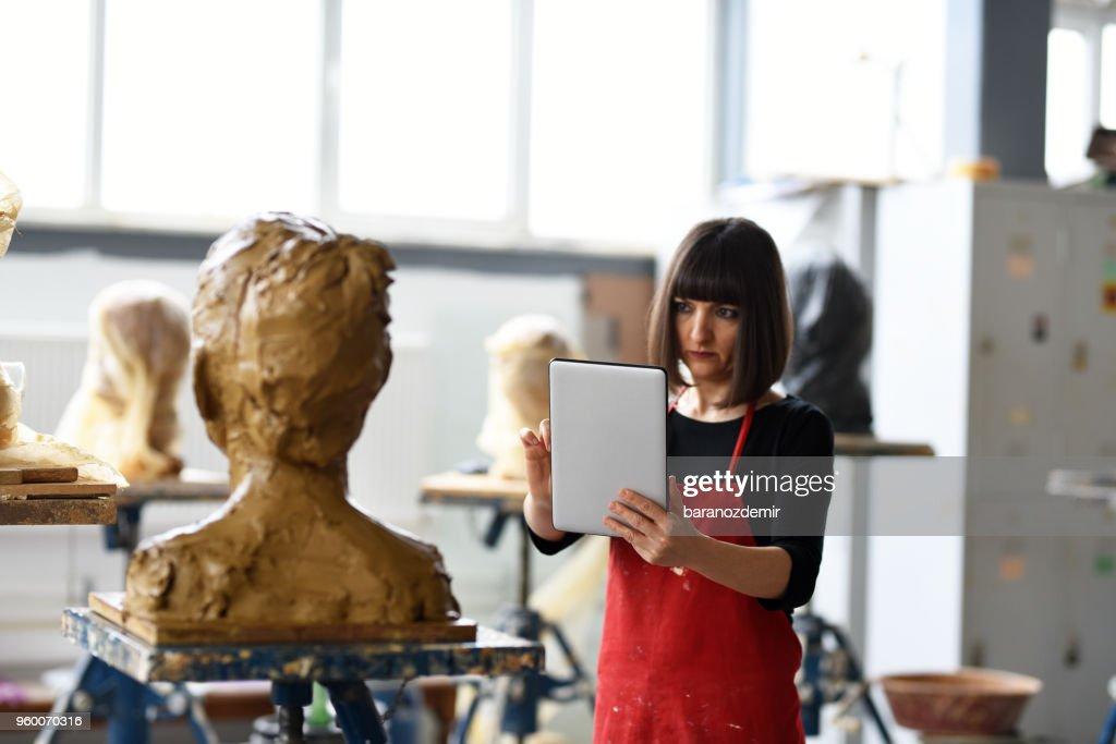 Junge weibliche Bildhauer arbeitet mit digital-Tablette in ihrem Atelier : Stock-Foto