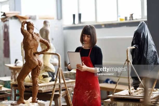 Young Female Sculptor is working with digital tablet in her studio