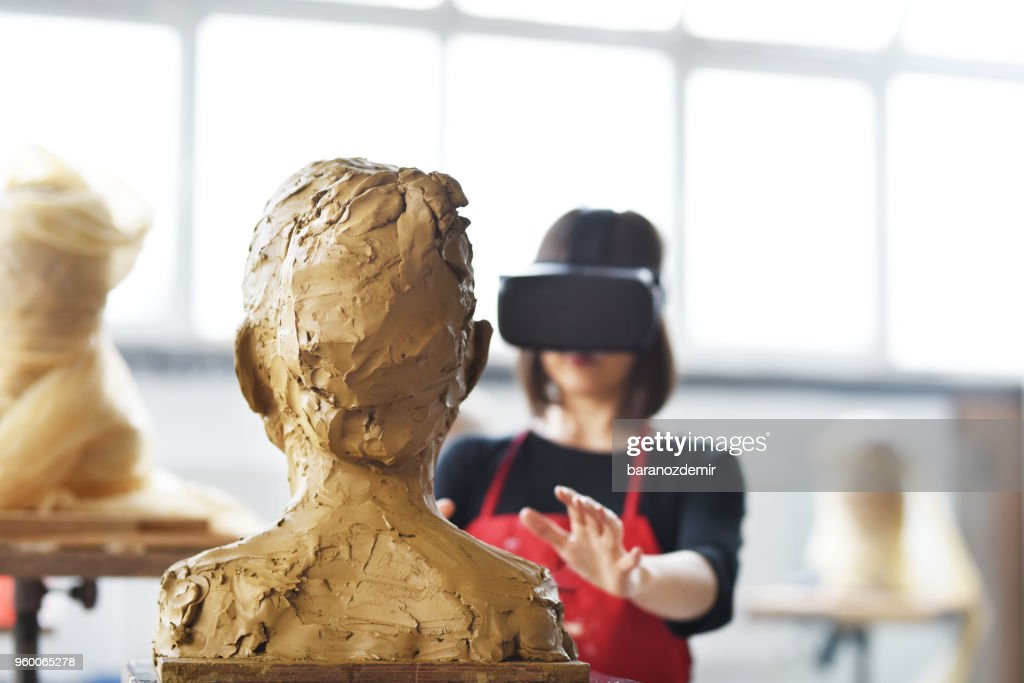 Young Female Sculptor is working with VR in her studio : Stock Photo