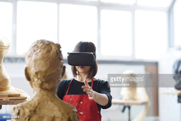 Young Female Sculptor is working with VR in her studio