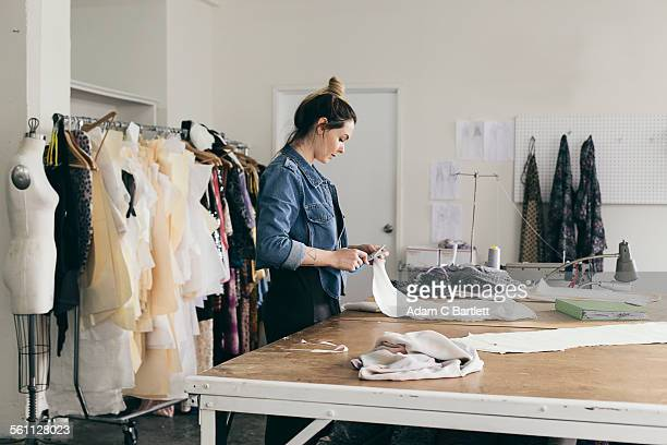 Young female seamstress cutting pattern in fashion studio