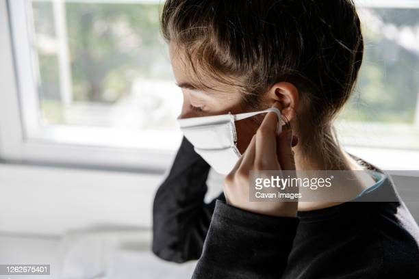 young female seamstress trying on a freshly made fabric face mask - ear stock pictures, royalty-free photos & images