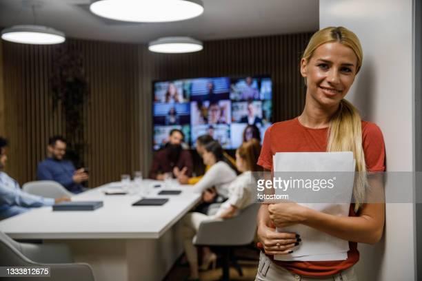 giovane segretaria donna che tiene i documenti e sorride alla telecamera prima di entrare in una riunione - big tech foto e immagini stock