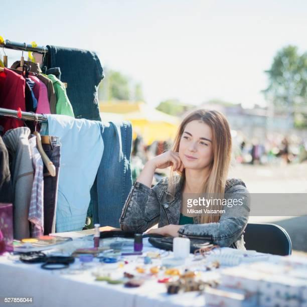 Young female seller on flea market