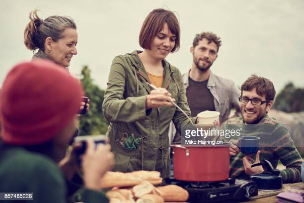 Young female serving soup to friends in their community allotment