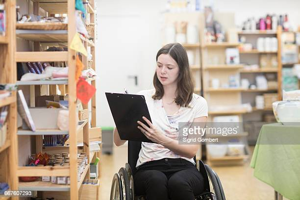 young female shop assistant using wheelchair stocktaking in shop - sigrid gombert stock pictures, royalty-free photos & images