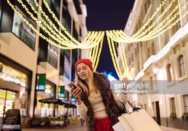Young female shopper reading smartphone texts on street at xmas, London, UK