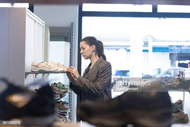 young female shopper selecting trainer in shoe shop - sigrid gombert imagens e fotografias de stock