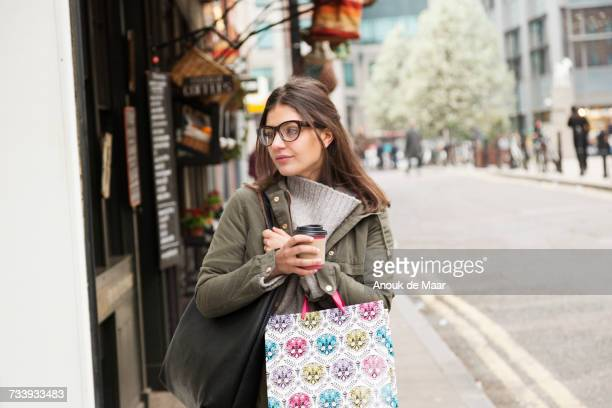 young female shopper with takeaway coffee strolling on street - parka coat stock photos and pictures