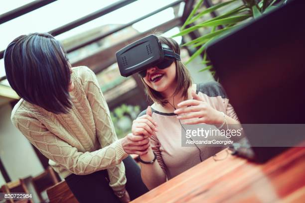 young female showing how virtual reality simulator and gesturing works and having fun - aleksandar georgiev stock photos and pictures