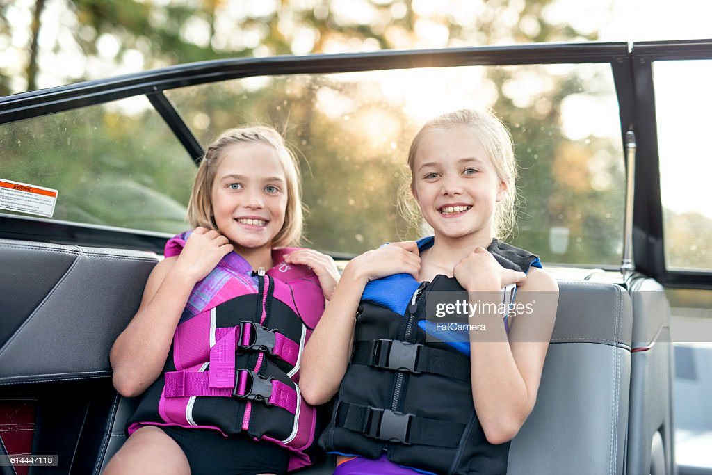 Young female siblings smile while wearing lifejackets : Stock Photo