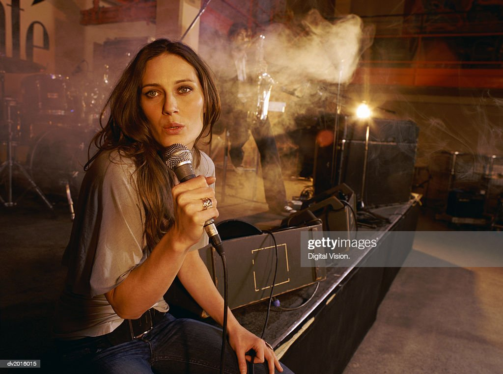 Young Female Singer Performs With a Band on a Smokey Stage : Stock Photo