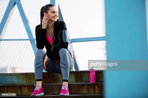 Young female sitting at stairs after running