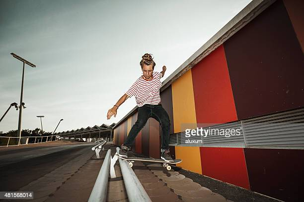Young female skateboarder grinding