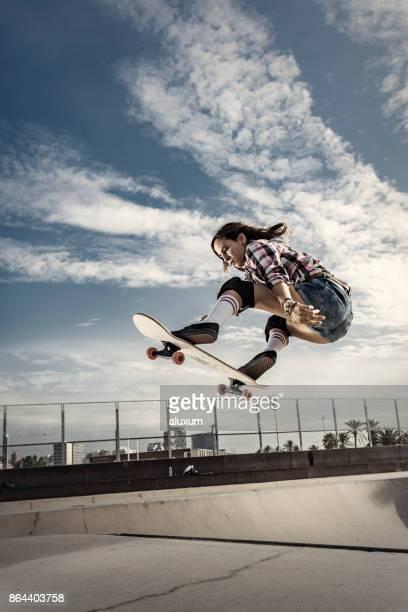 Jonge vrouwelijke skateboarder springen in skateboard park in Barcelona Catalonië Spanje