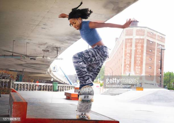young female skateboarder practicing a difficult jump - skating stock pictures, royalty-free photos & images