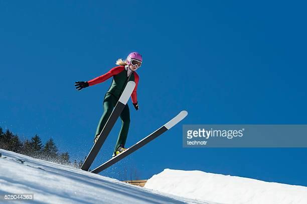 若い女性のスキージャンプランディングを、ブルースカイ