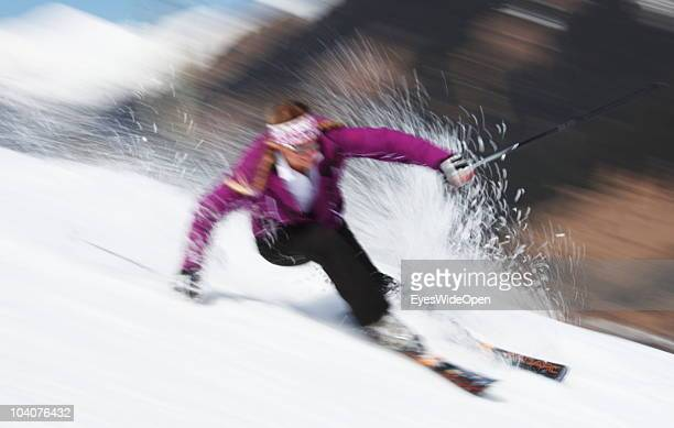 A young female skier is carving on the slope and the snow is spraying on March 19 2010 in Lermoos Tyrol Austria