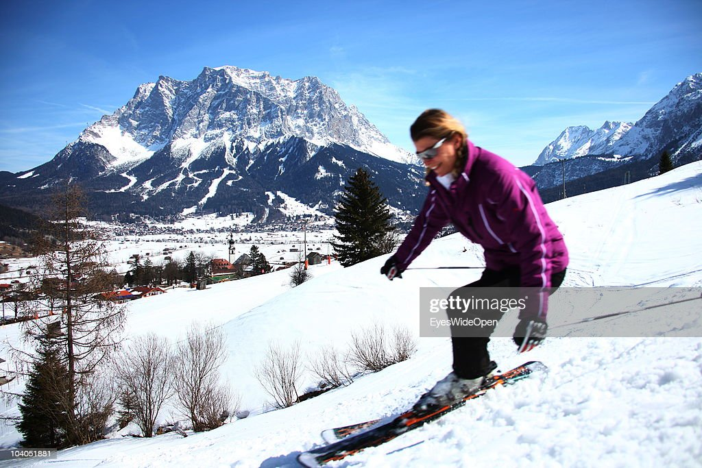 A young female skier is carving on the slope with panoramic view of the mountain Zugspitze on March 19, 2010 in Lermoos, Tyrol, Austria. The Zugspitze has got an altitude of 2962 meters and is the highest mountain and only glacier of Germany.