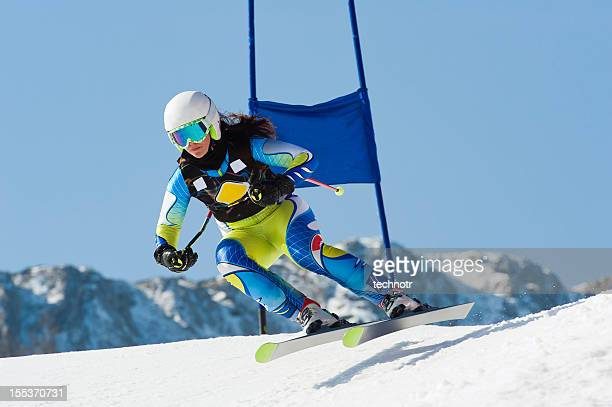 Young female skier jumping during the downhill race