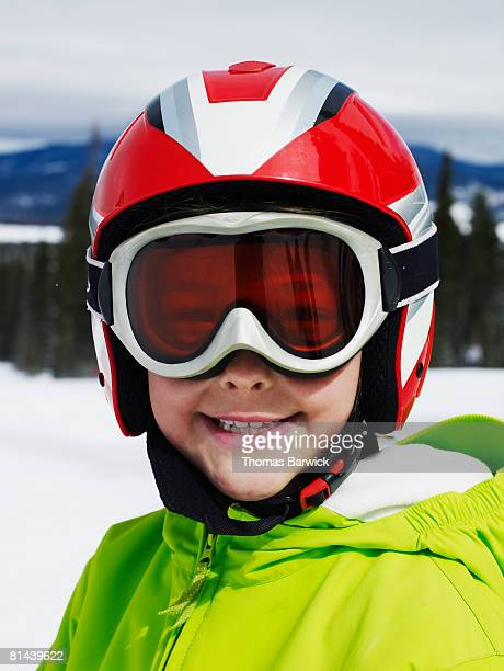 Young female skier wearing helmet and goggles, smiling.