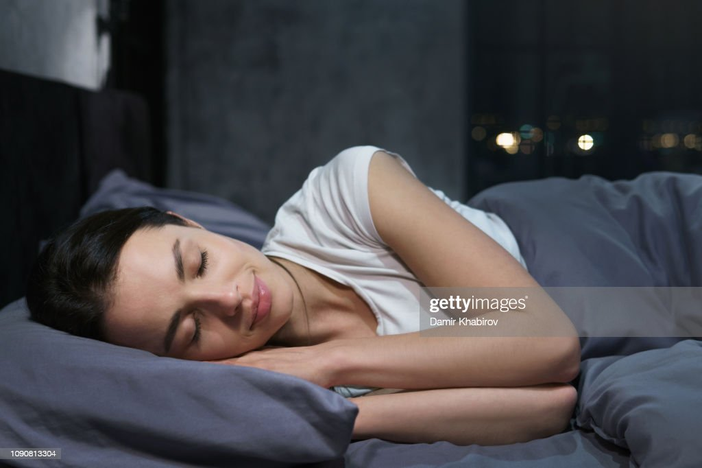 Young female sleeping peacefully in her bedroom at night, relaxing : Stock Photo