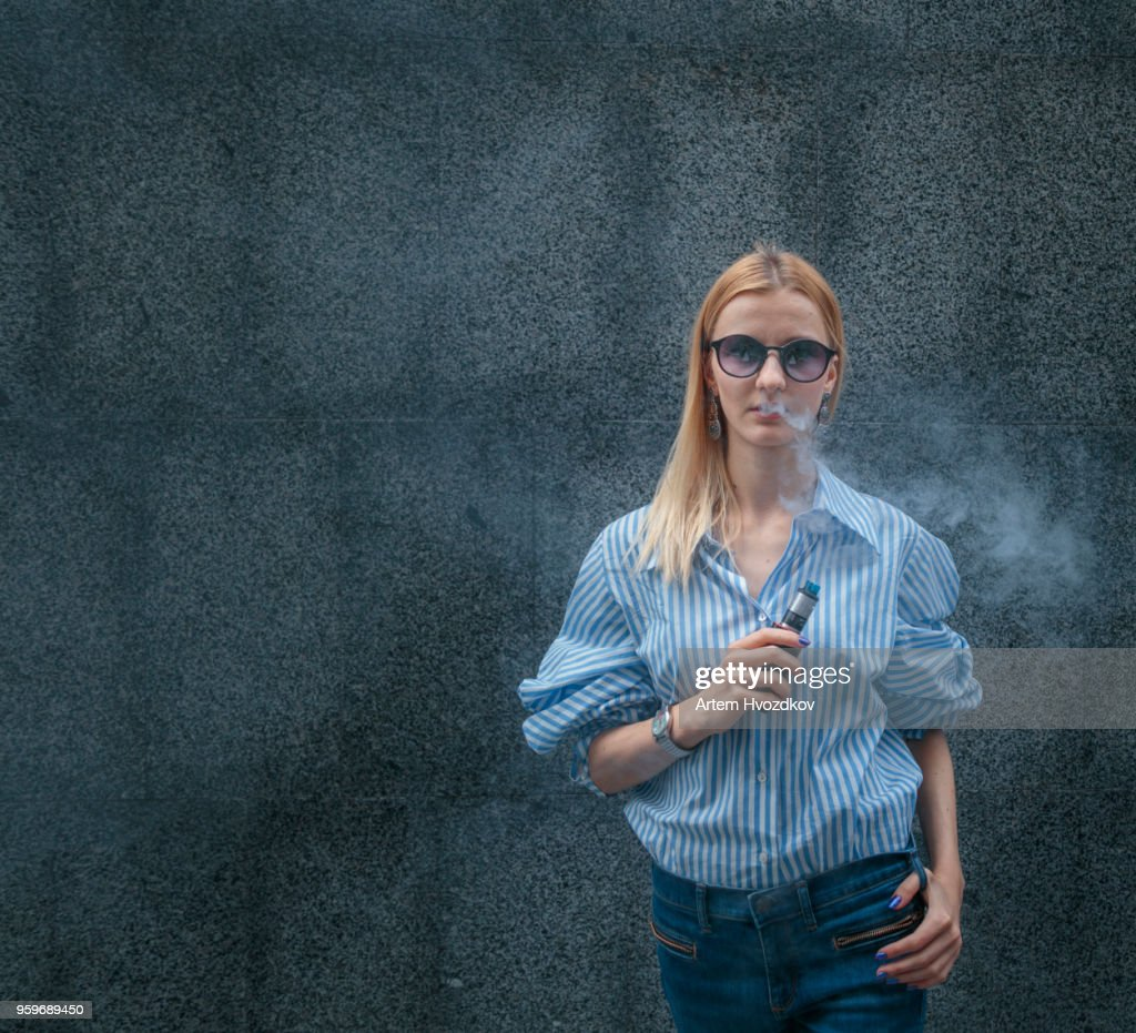 Young female smoking electronic cigarette : Stock-Foto